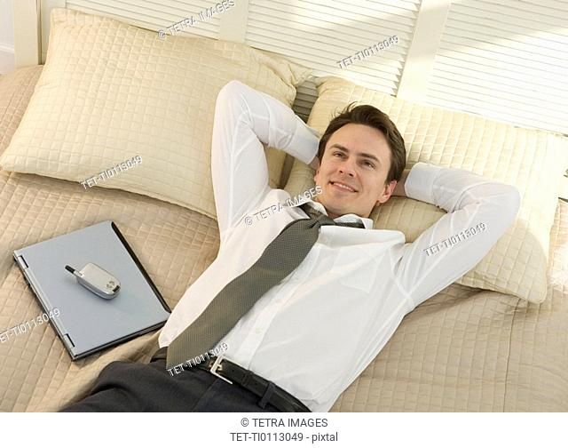 Closeup of businessman resting on bed