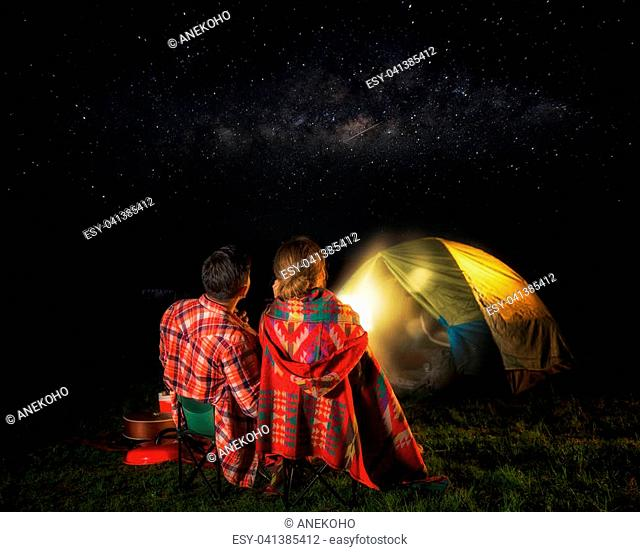 Picknic and camping concept, man and lady sit and look at star, milky way and meteor, love and valentine day
