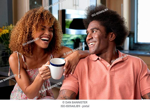 Mid adult woman and mature man laughing over coffee
