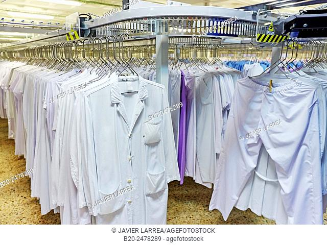 Lab coats hanging on rack in automated warehouse of hospital laundry, Hospital Donostia, San Sebastian, Basque Country, Spain