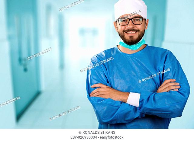 happy smiling doctor surgeon standing in the hospital hallway
