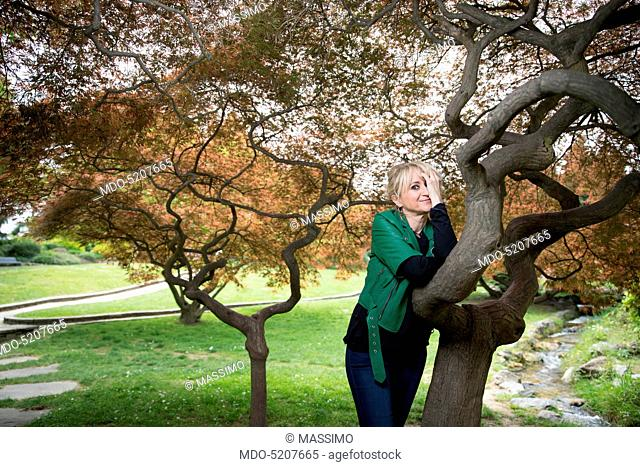 Actress and comedian Luciana Littizzetto leaning against a tree inside the public park Parco del Valentino. Turin, Italy. 21st April 2016