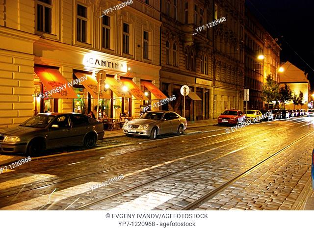 Prague street with tram lines at night: cars, cafe, lights
