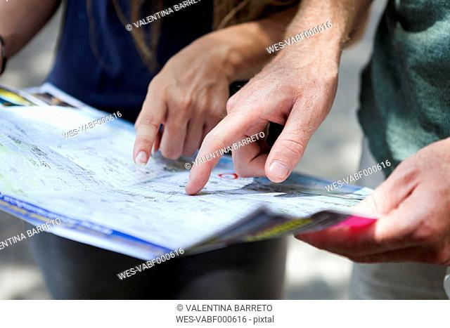 Couple's hands pointing on city map