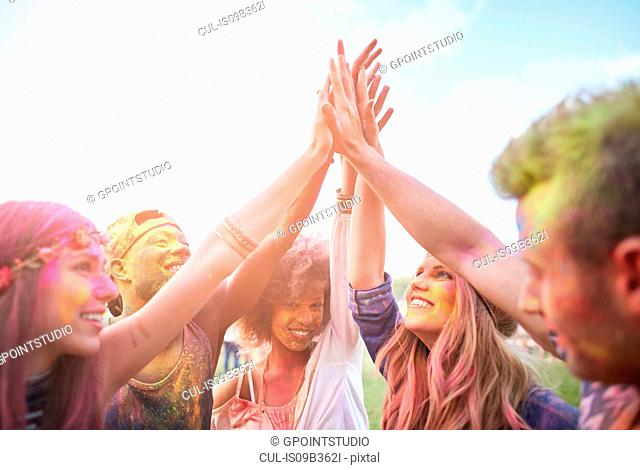 Group of friends at festival, covered in colourful powder paint, joining hands