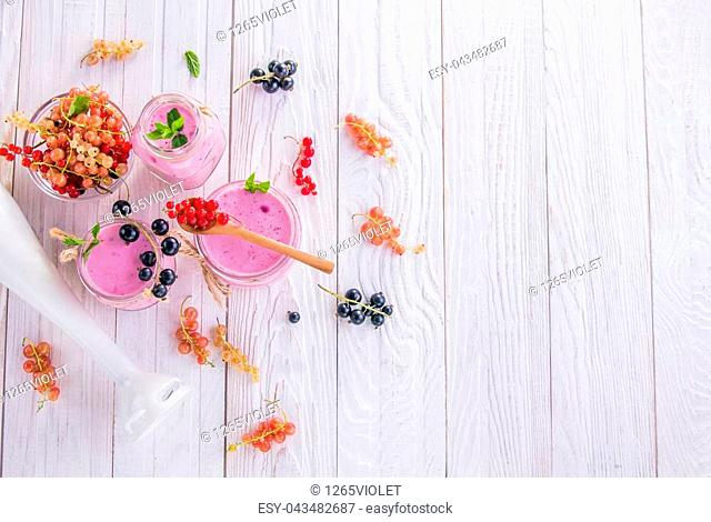 Fruity smoothie in glasses with red, white and black currant on white wooden background. Healthy eating. Organic food