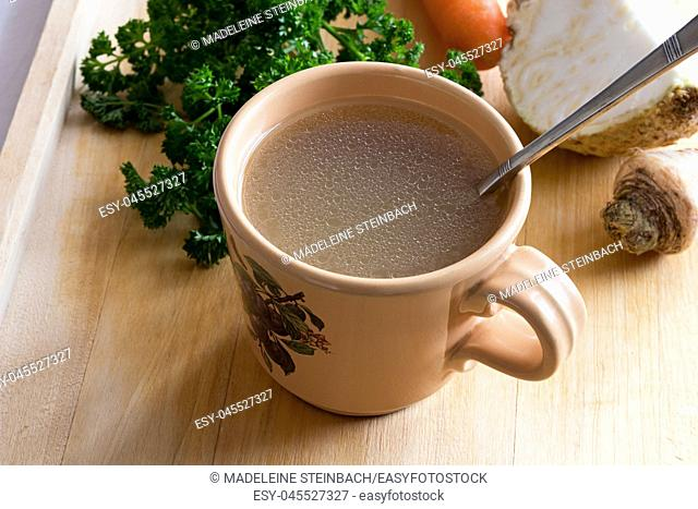 Chicken stock in a vintage mug with a spoon, with parsley, carrot and celery root in the background