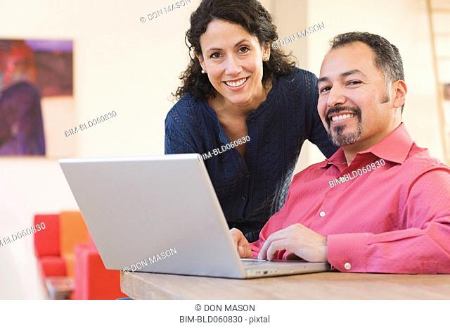 Hispanic couple next to laptop