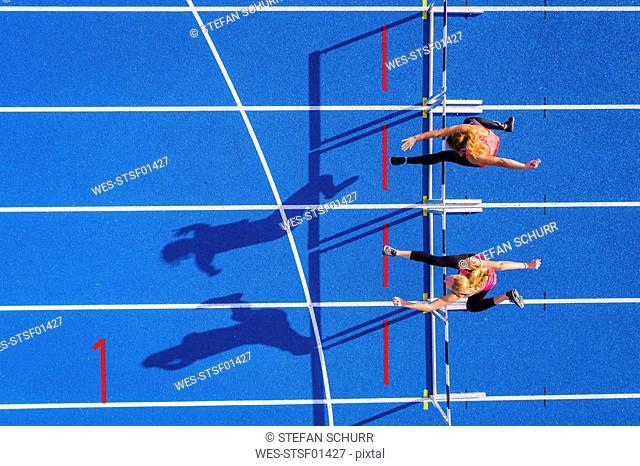 Top view of two female runners crossing hurdles on tartan track