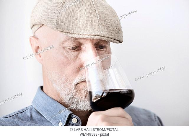 Old man in cap holding wineglass. Smelling the red wine with serious expression