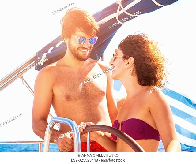 Cheerful couple driving sailboat, handsome guy and cute girl laughing and looking with love on each other, enjoying active summer vacation