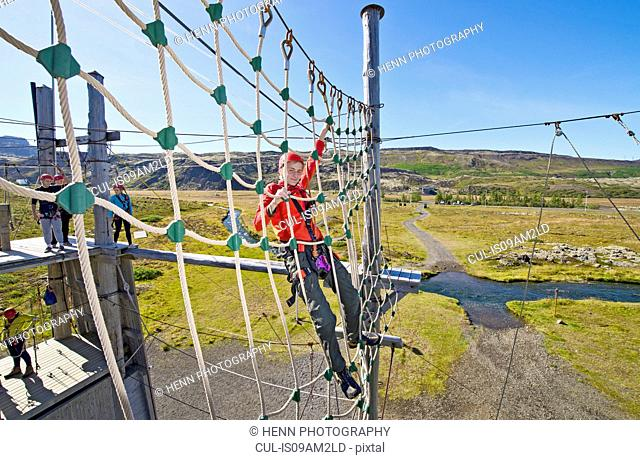 Teenage boy climbing on ropes at high rope course
