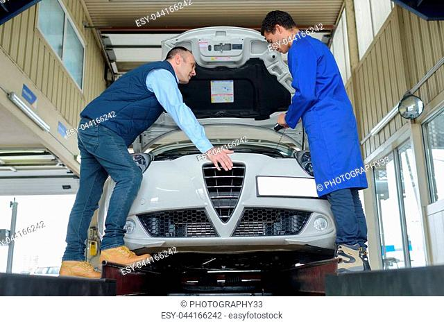 mechanics checking car engine
