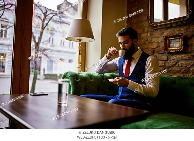 Fashionable young man sitting on couch in a cafe drinking coffee and using cell phone
