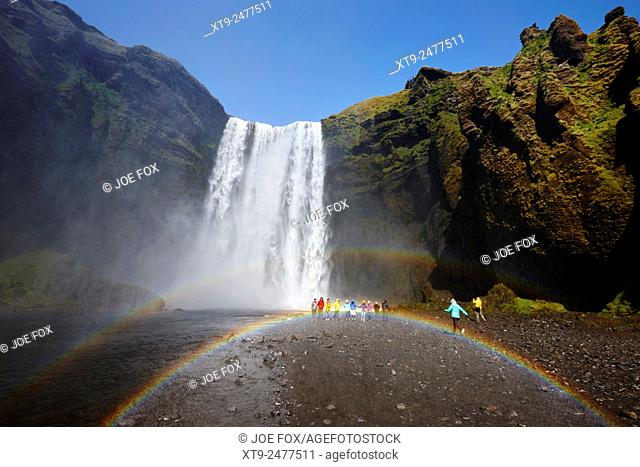 crowds of tourists with double rainbow at skogafoss waterfall in iceland