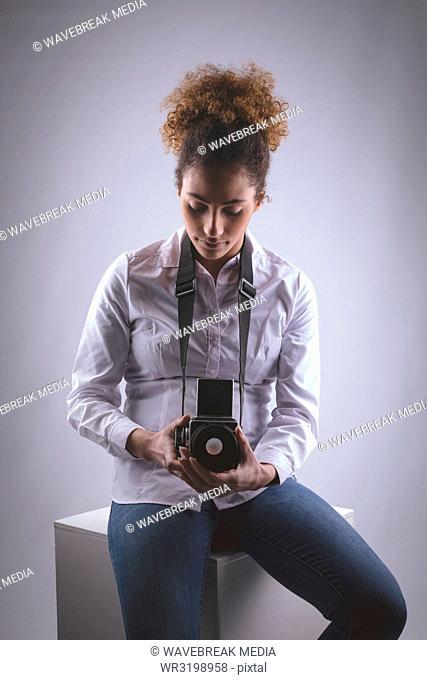 Female photographer clicking photos in photo studio
