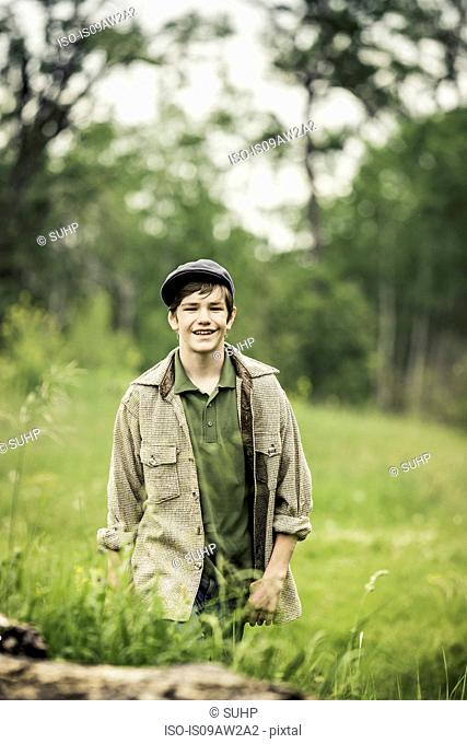 Teen boy wearing flat cap in tall grass looking at camera smiling