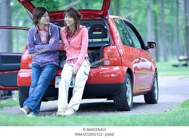 Young Couple Sitting on Vehicle Trunk and Chatting