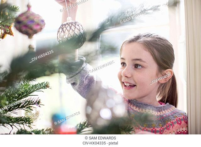 Girl decorating, hanging ornament on Christmas tree