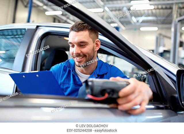 service, repair, maintenance and people concept - mechanic man with automotive diagnostic scanner and clipboard checking car system at workshop
