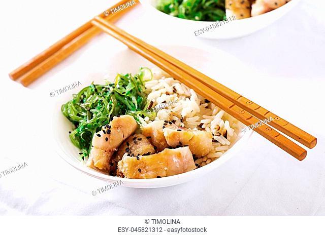 Japanese food. Bowl of rice, boiled white fish and wakame chuka or seaweed salad