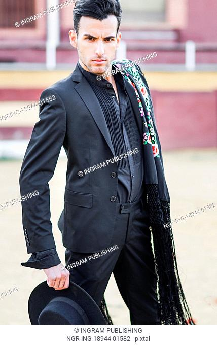 Portrait of a handsome man, model of fashion, wearing spanish clothes in a bullring