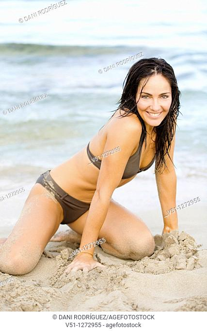 Portrait of a sexy brunette woman smiling at camera at the beach