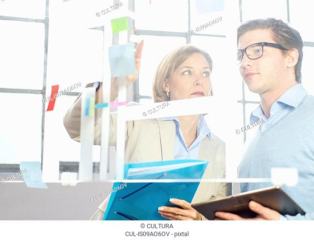 Businessman and woman pointing at idea notes on office glass wall