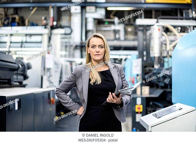 Portrait of confident woman holding tablet in factory shop floor