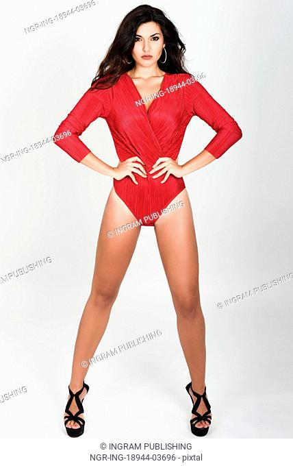 Young woman wearing red body and earrings on white background. Brunette girl with long hair and wavy hairstyle looking to camera. Studio shot