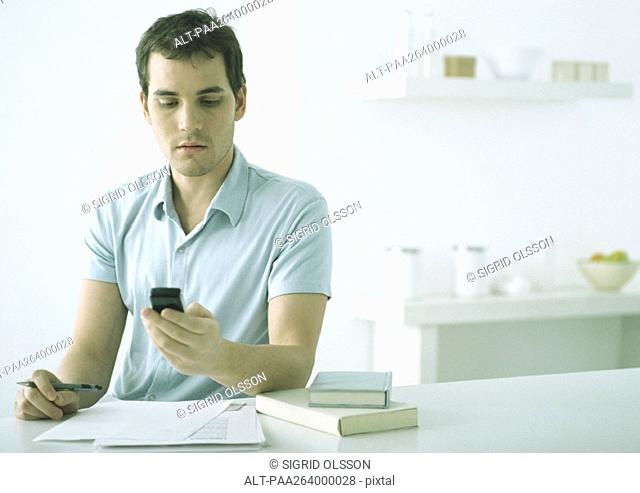 Young man at table with paper and books, looking down at cell phone