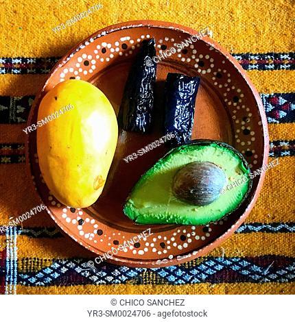 Mango, avocado and chilli in a yellow Morrocan carpet in Coyoacan, Mexico City, Mexico