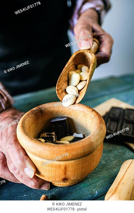 Man's hands pouring almonds in a wooden bowl