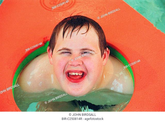 Teenage boy with Downs Syndrome playing with coloured float in public swimming pool