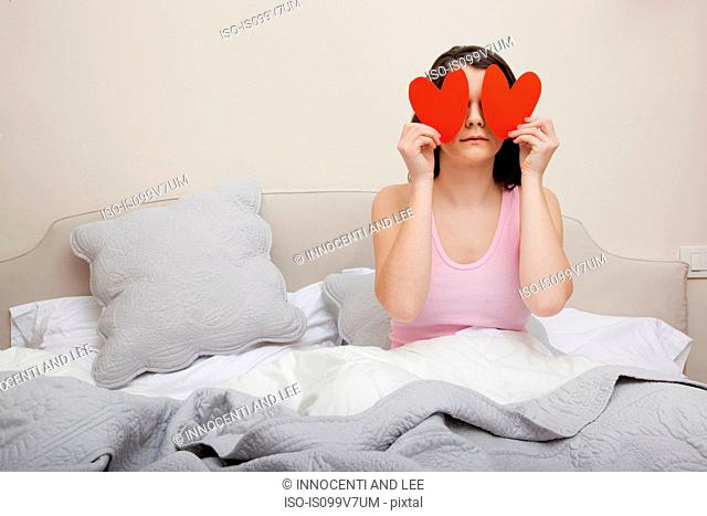 Woman in bed holding heart shapes over eyes