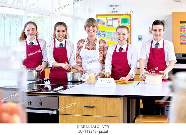 Portrait confident teacher and high school students in home economics class
