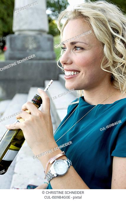 Mid adult woman sitting on park stairs drinking beer