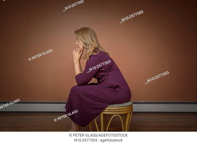 Blond woman sitting on a stool