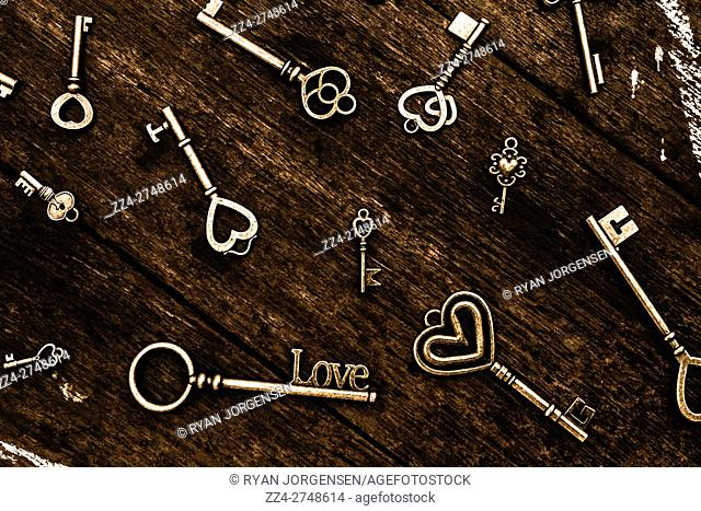 Collection of different love and romance themed keys with hearts or the word Love scattered over a wooden table viewed from above