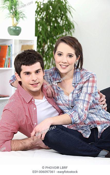 Couple hugging on white sofa