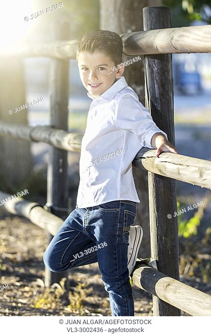 Charming stylish boy posing on rural fence looking confidently at camera