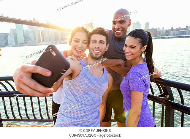 Four adult running friends taking smartphone selfie on riverside, New York, USA