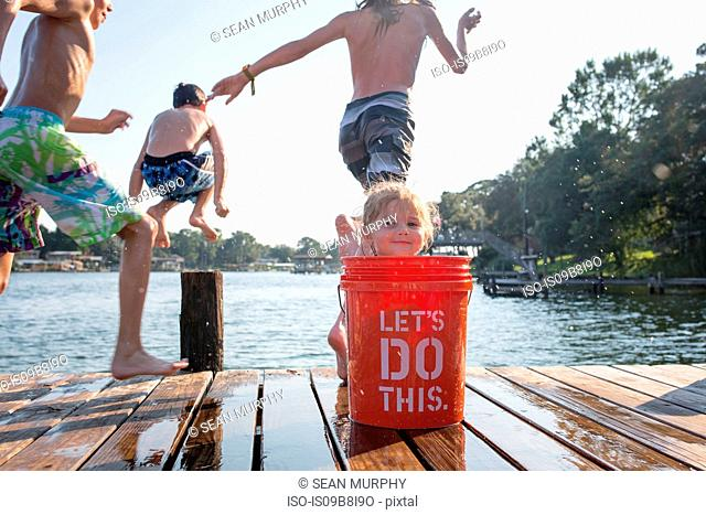 Young girl hiding behind bucket on jetty, children jumping into lake