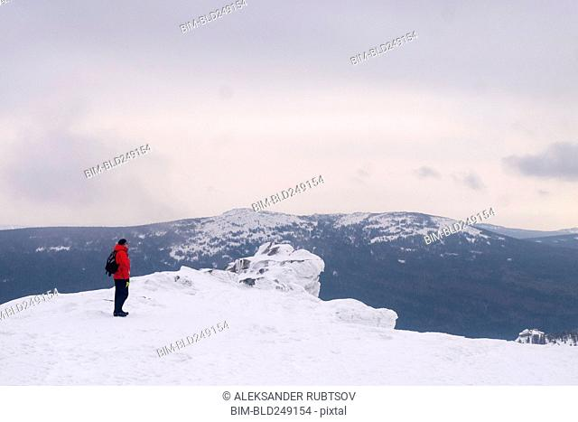 Caucasian man standing on remote mountain in winter