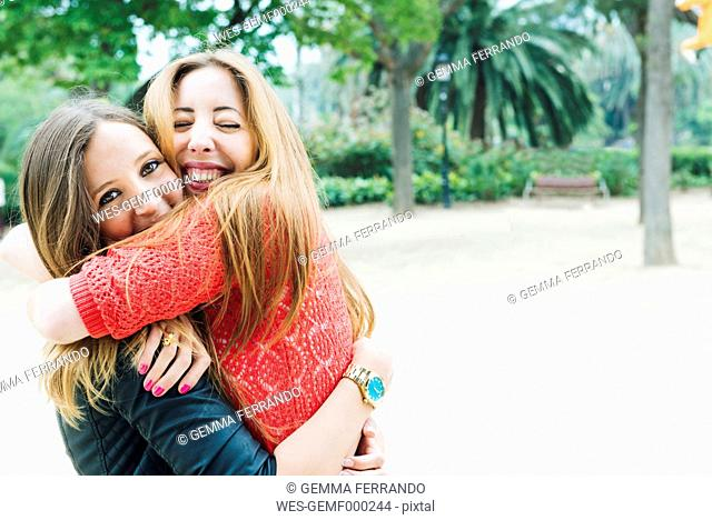 Two happy young women hugging in a park