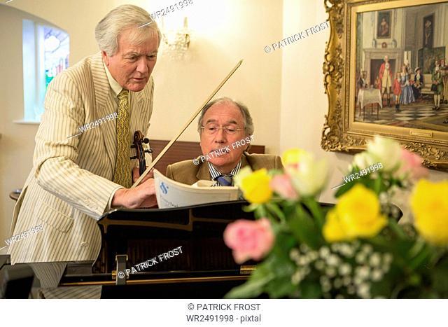 Two senior men playing music together