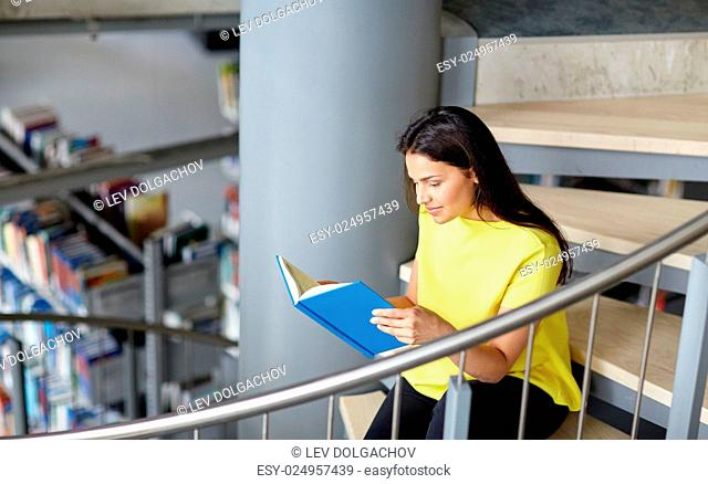 education, high school, university, learning and people concept - smiling student girl reading book sitting on stairs at library