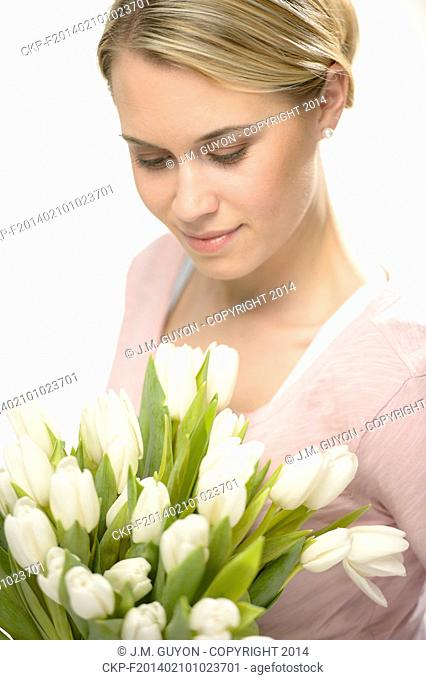 Lovely woman looking down white spring flowers bouquet of tulips