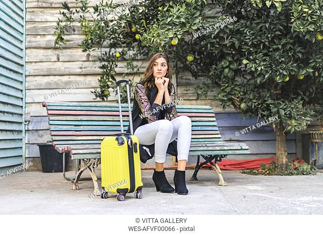 Young woman with a yellow trolley bag waiting on a bench