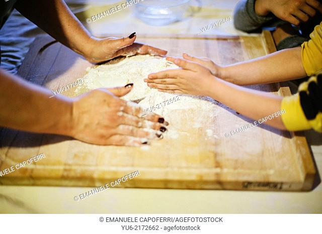 Hands of mother and sons in the flour and mix the ingredients to make a cake